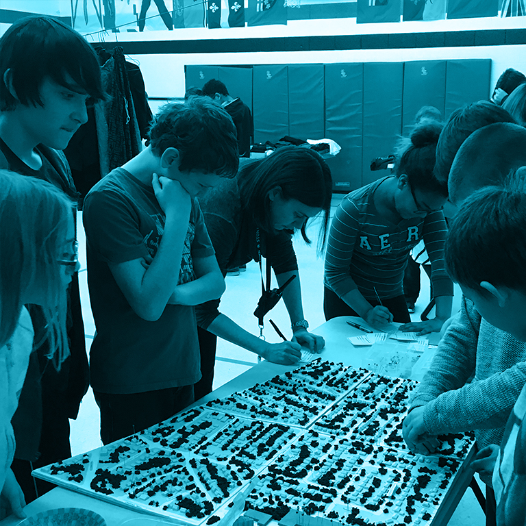 Image of seven youth engaging with a 3-D neighbourhood model